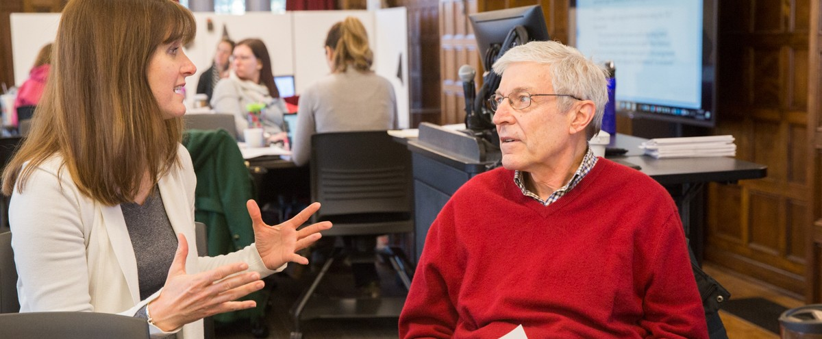 A woman in white jacket talking animatedly to an older man wearing a red sweater